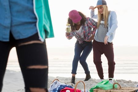 Three young female friends fooling around at beach picnic, Cape Town, Western Cape, South Africa
