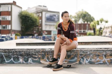 brixton: Female skateboarder sitting in skatepark LANG_EVOIMAGES