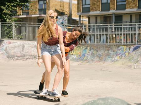 brixton: Two women practising skateboarding balance in skatepark