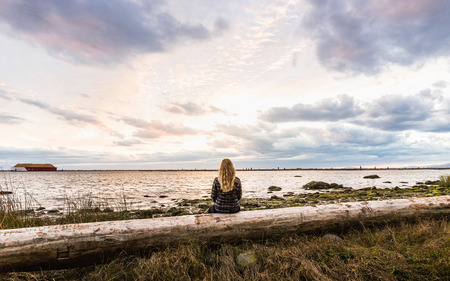 Rear view of woman sitting on tree trunk looking out from Wreck Beach at dusk, Vancouver, Canada LANG_EVOIMAGES