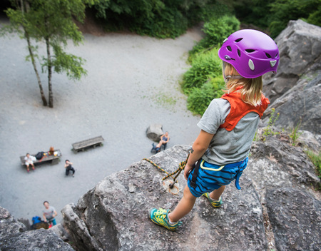 Boy wearing climbing helmet standing on top of rock looking down