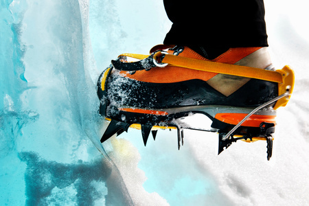 crampon: Cropped view of ice climbers feet wearing crampons