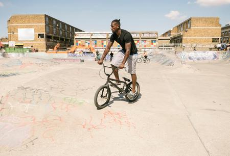 brixton: Young man riding BMX bicycle in skatepark LANG_EVOIMAGES