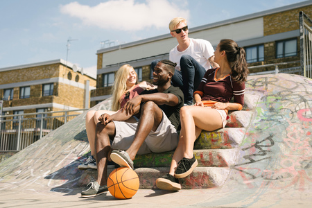 brixton: Four male and female basketball friends sitting chatting in city skatepark LANG_EVOIMAGES
