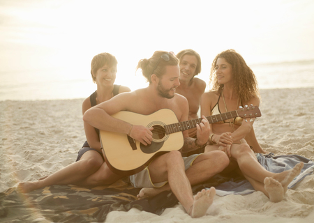 age 25 30 years: Group of friends sitting on beach, man playing guitar
