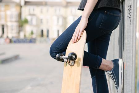 brixton: Waist down of female skateboarder leaning against fence in skatepark