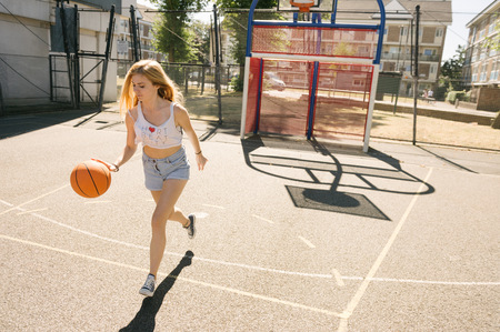 Young woman running with ball on basketball court LANG_EVOIMAGES