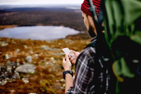 Hiker checking compass on cliff top, Keimiotunturi, Lapland, Finland