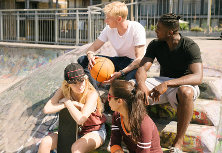 brixton: Male and female basketball friends chatting in city skatepark LANG_EVOIMAGES