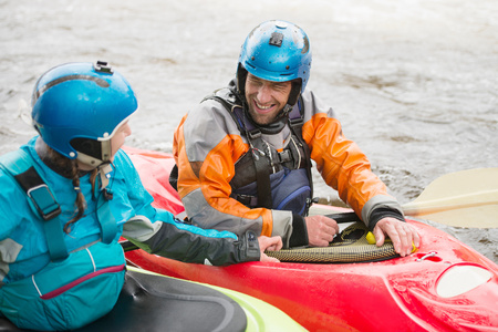 25 35: Male and female kayakers talking on River Dee LANG_EVOIMAGES