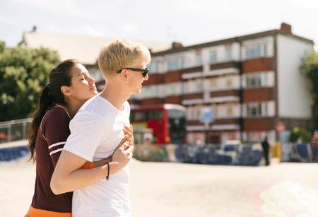 brixton: Woman hugging boyfriend in city skatepark LANG_EVOIMAGES