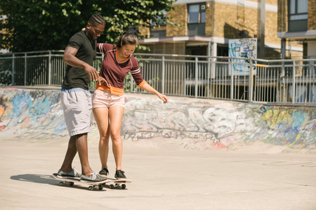 Young man and woman practising skateboarding balance in skatepark LANG_EVOIMAGES