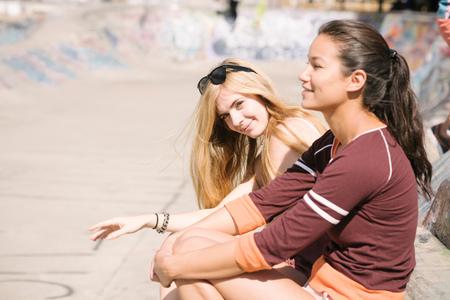 brixton: Two female skateboarders sitting in skatepark