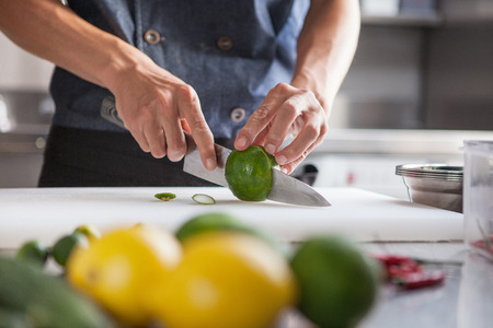 Cropped view of man slicing limes LANG_EVOIMAGES