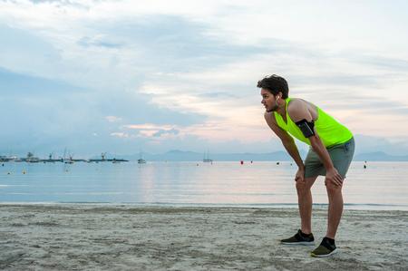 mallorca: Man on beach, hands on knees looking exhausted, Mallorca, Spain