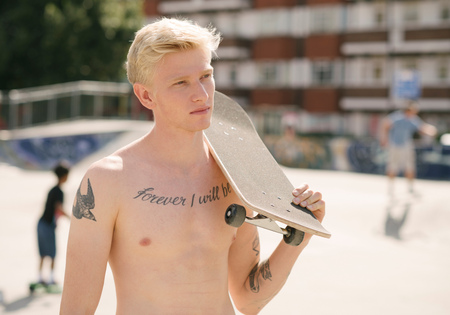 brixton: Tattooed young man carrying skateboard on shoulder in skatepark LANG_EVOIMAGES