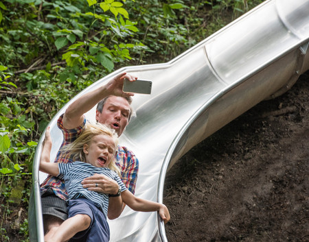 Father and son sliding down slide holding smartphone