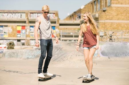 brixton: Young female and male skateboarding friends skateboarding in skatepark