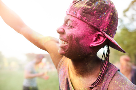 Young man at festival, covered in colourful powder paint, arms raised, dancing LANG_EVOIMAGES