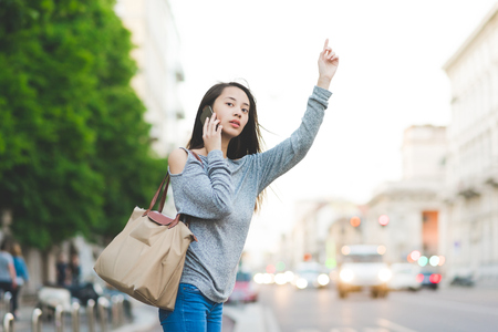 Young woman using smartphone whilst hailing a cab in city