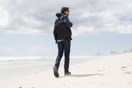 Rear view of young man strolling alone on beach, Western Cape, South Africa