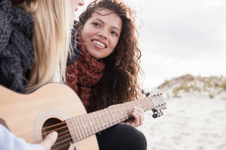 Two young female friends playing guitar at beach, Western Cape, South Africa