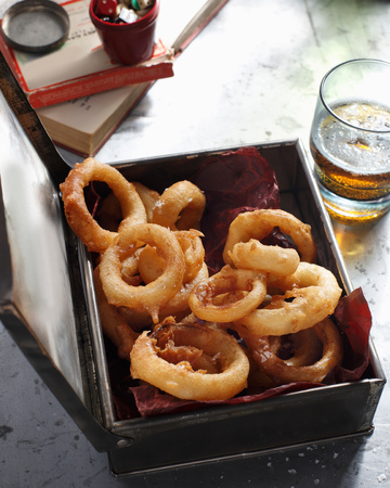 generosidad: Bistro meal of deep fried onion rings and beer on table