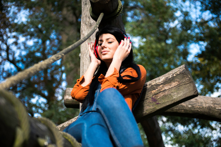 dungarees: Young woman sitting on wooden climbing frame, wearing headphones