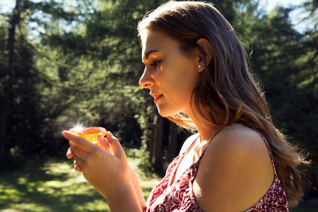 Young woman gazing at yellow crystal in forest, Sattelbergalm, Tyrol, Austria