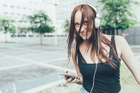 Portrait of young woman listening to headphones and dancing outside office building LANG_EVOIMAGES