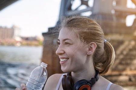 Young woman beside river, wearing headphones around neck, holding water bottle, New York City, USA LANG_EVOIMAGES