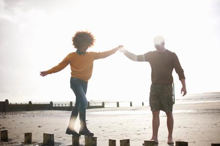 Man helping woman balance on wooden stumps on beach