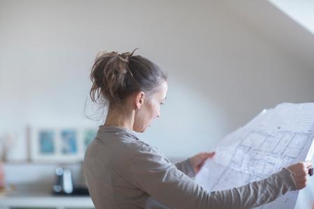 Mature woman looking at blueprints