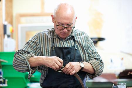65 69 years: Male worker in leather workshop, polishing belt buckle