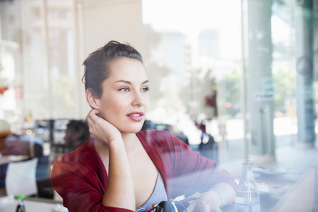 Young woman sitting in cafe, looking out of window LANG_EVOIMAGES