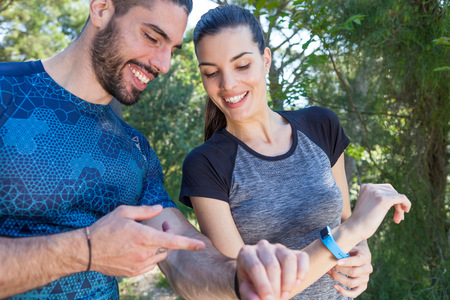 Male and female runners checking smartwatches in park, Split, Dalmatia, Croatia LANG_EVOIMAGES