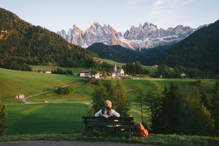 Woman relaxing on park bench, Santa Maddalena, Dolomite Alps, Val di Funes (Funes Valley), South Tyrol, Italy