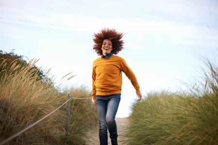 Woman running down grassy dune