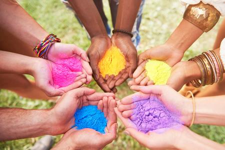Groep vrienden bij festival, die kleurrijke poederverf in tot een kom gevormde handen, close-up houden LANG_EVOIMAGES