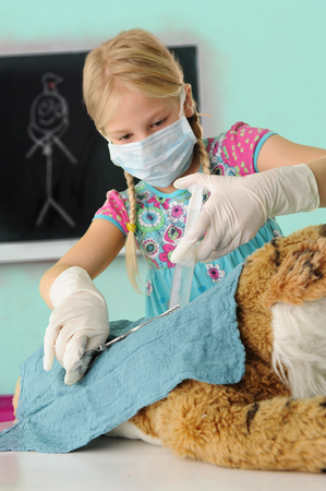 anaesthetic: Girl pretending to be vet giving toy tiger syringe injection during operation LANG_EVOIMAGES