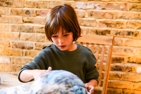 Child playing with papier mache