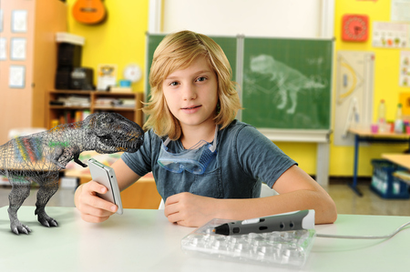 Portrait of boy with hand held computer and 3D model of tyrannosaurus rex LANG_EVOIMAGES