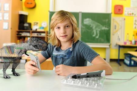 educacion ambiental: Retrato de niño con computadora de mano y modelo 3D de tiranosaurio rex LANG_EVOIMAGES