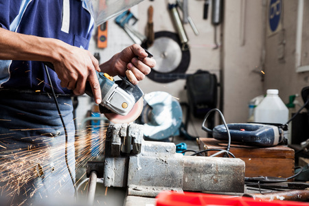 Mid section of young man using angle grinder in repair workshop