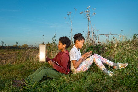 pantalones abajo: Niños que usan una célula solar en miniatura para alimentar una tableta digital, Breda, Países Bajos LANG_EVOIMAGES