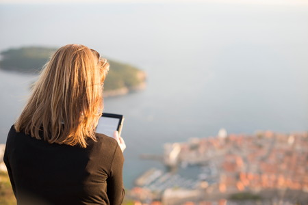 electronic book: Rear view of woman using digital tablet, Dubrovnik, Croatia