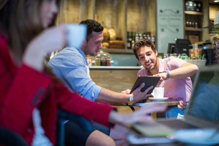 Male friends sitting in cafe pointing at digital tablet