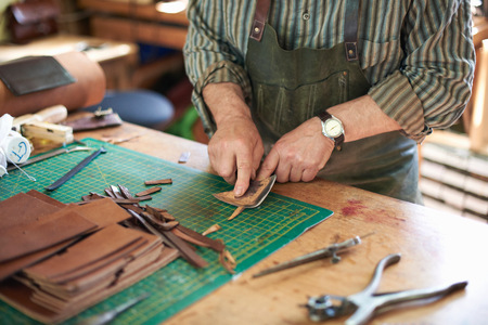 65 69 years: Male worker in leather workshop, checking sharpness of knife on leather, mid section