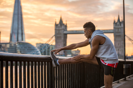 Man stretching against railing, Tower Bridge and The Shard in background, Wapping, London, UK LANG_EVOIMAGES