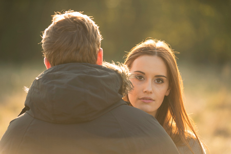 Young couple in field, young woman looking over mans shoulder LANG_EVOIMAGES